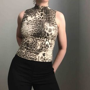 Så unik topp i stretchigt material med leoprint • hög krage och utan ärmar • ingen storlek men sitter som en XS • i bra skick!