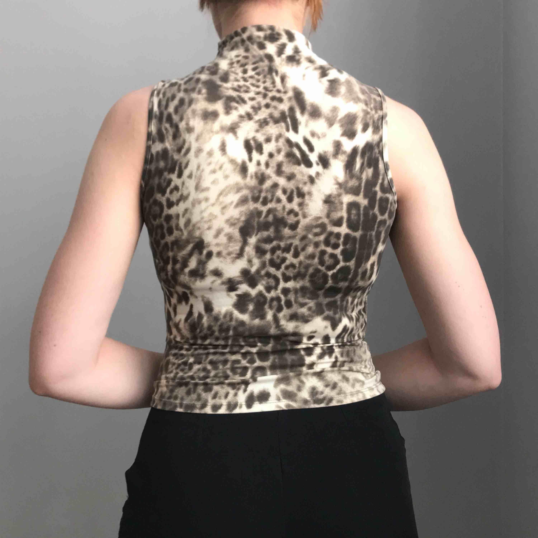 Så unik topp i stretchigt material med leoprint • hög krage och utan ärmar • ingen storlek men sitter som en XS • i bra skick!. Toppar.