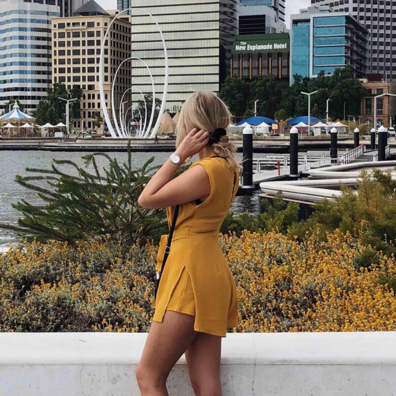 Gul playsuit i storlek S. Endast använd en gång.  Köpt i en affär i Australien. Figursydd med dragkedja baktill. Passar mig bra som är 165 lång och har xs/s i kläder. 150kr INKL frakt! . Klänningar.