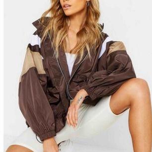 En oversize jacka i brun och vita och beiga detaljer. Luva som man kan ha ute men också stoppa in. Använd 2 gånger