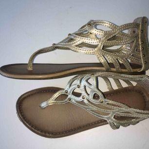 Guldiga sandaler i stl 35. Dragkedja bak på hälen. Kan synas lite slitningar men annars väldigt fina! Kontakta om ni vill ha fler bilder eller vid intresse.  Skickar gärna men köparen får stå för frakt! 😊💗☀️
