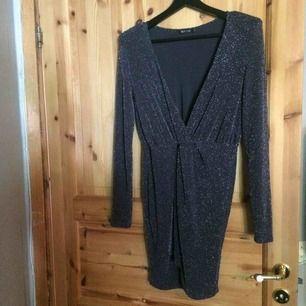 Glittrig klänning med puffar på axlarna, har endast blivit använd en gång. Har små skavanker, men inget som märks. (se bild tre) Fraktkostnad tillkommer på 40kr.