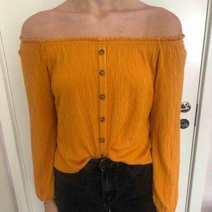 Jättefin senapsgul tröja/topp (off-shoulder) med prydnads knappar. Nyskick!! Kan mötas upp i Stockholm eller frakta (köparen betalar).