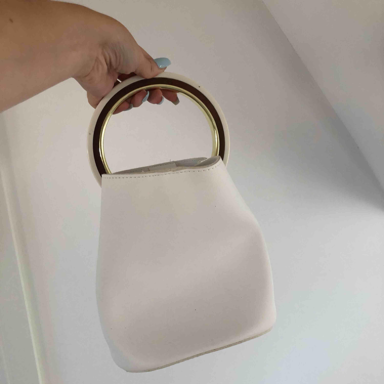 Helt oanvänd väska från Nelly (prislapp kvar!). Saknas axelremskedjan men annars helt som ny.. Väskor.