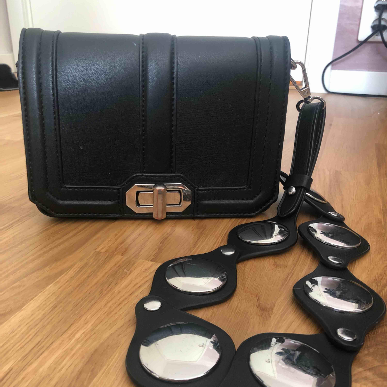 Fin svart väska med coolt band från Gina! Kan mötas upp i Stockholm eller frakta (köparen betalar).. Accessoarer.