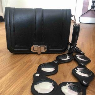 Fin svart väska med coolt band från Gina! Kan mötas upp i Stockholm eller frakta (köparen betalar).