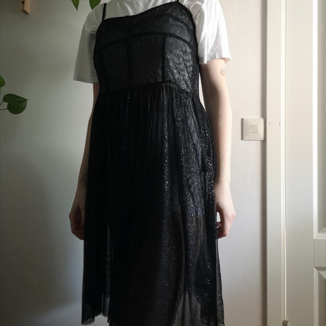 Glittrig och väldigt genomskinlig klänning. Har en vit
