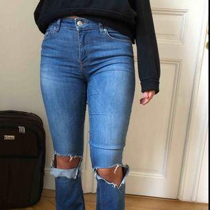 Snygga bootcut jeans med hål på knäna från Zara. Storlek 36. Lite slitna längst ner på byxan.