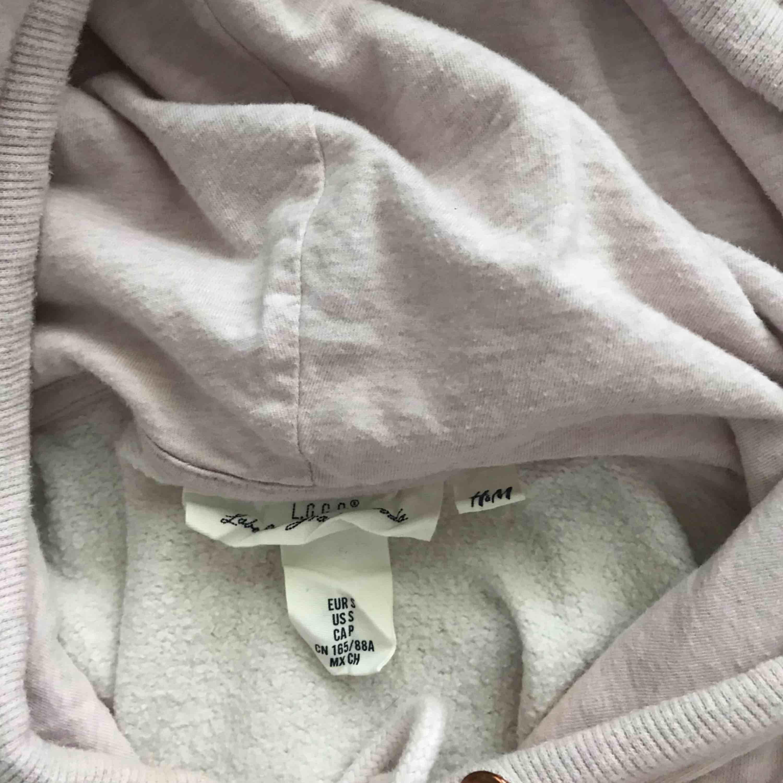 Ljusrosa hoodie från hm med tryck i rosé/guld. Huvtröjor & Träningströjor.