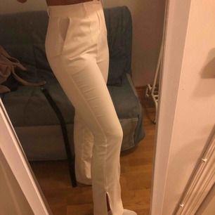 Oanvända vita bootcut kostymbyxor med slits.