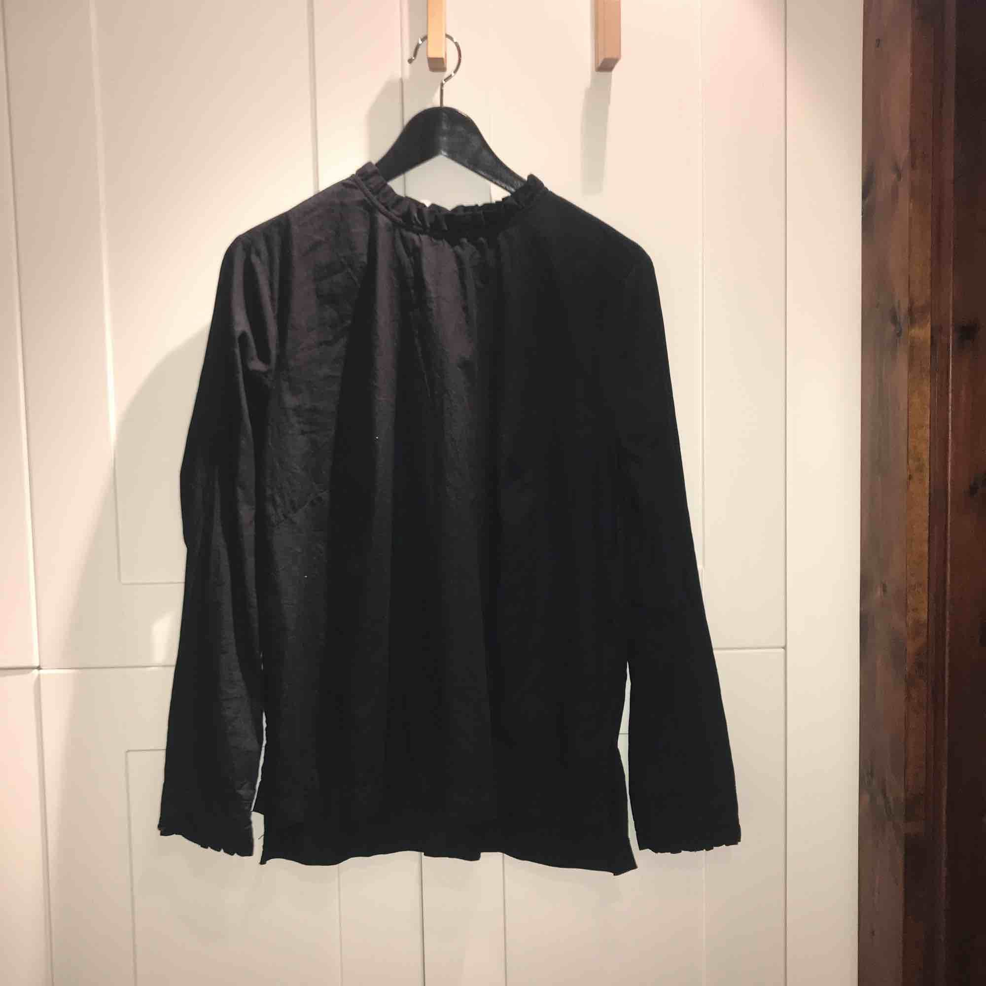 Svart blus med volang längs kragen, stl. 44 (passar en 38-40 också!) från H&M!. Blusar.