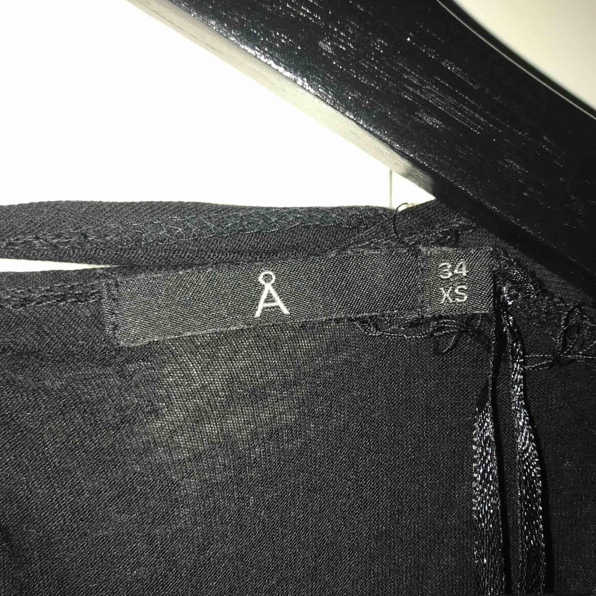 Svart klänning med omlott-rygg i stl. 34/XS från Åhléns. Klänningar.