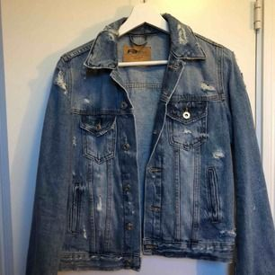 Jeans jacka med slitningar.
