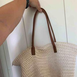 En vit mjuk stråväska från h&m med tygklädd insida i mycket fint skick. Inga fläckar och knappt använd