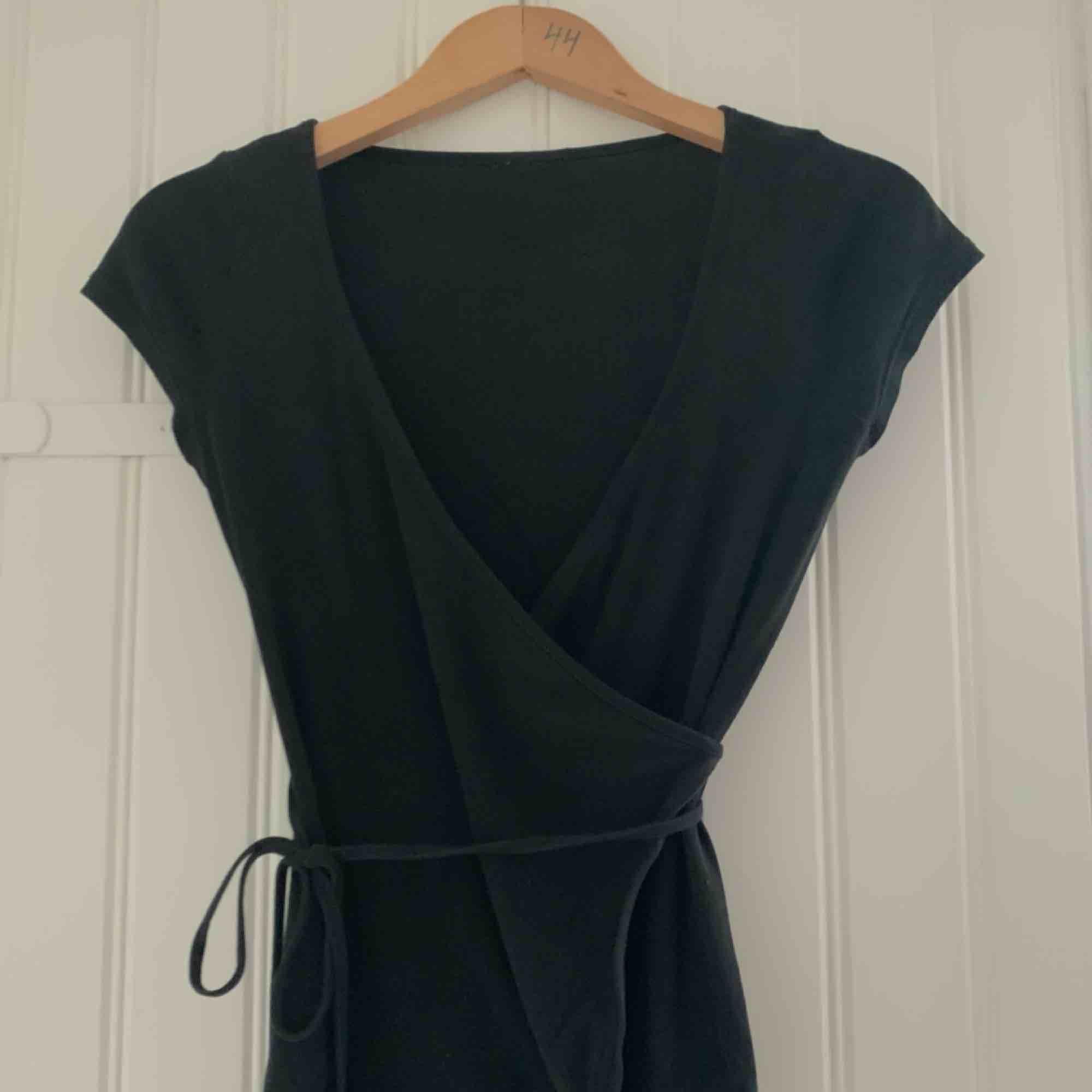 En wrap-around (omlott) tröja med knytning i sidan. Storlek S ungefär, men den kan säkert passa XS-M, kanske även L! Ser ungefär ut som en svart T-shirt. Om man vill ha lite mindre urringning funkar den även utmärkt med ett linne under:). Toppar.