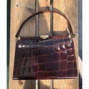 Söt liten handväska som jag köpt second hand men inte fått användning av. Brun med krokomönster, mocka invändigt. Mått: 24x17. Jättefint skick! Frakt på 59kr tillkommer ✨