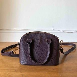 Säljer en superfin liten lila väska från märket Don Donna. 20 cm bred och 15 cm hög. Använd endast ett fåtal gånger. Kan bäras som handväska eller med axelremmar.