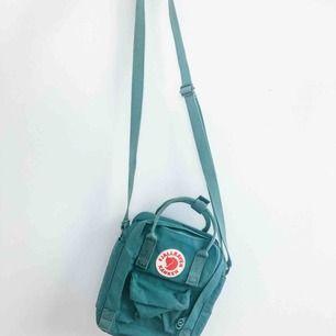 Säljer min Kånken Sling som är inköpt för ca 1 månad sen. Den är använd en gång, men blir tyvärr bara hängandes.  Nyskick, fristgrön, axelremsväska. ☘️