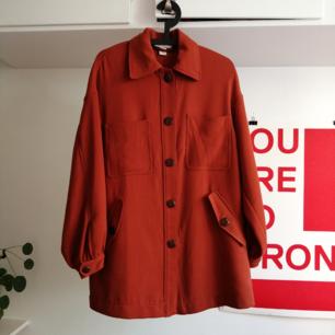 Rostfärgad overzise kappa från H&M. Går en bit över rumpan och har stora puffiga ärmar.