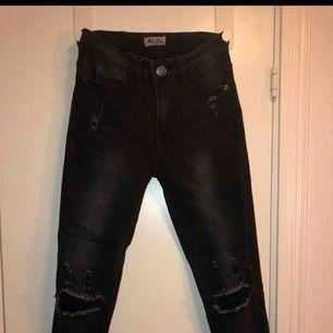Svarta jeans med hål på knäna.
