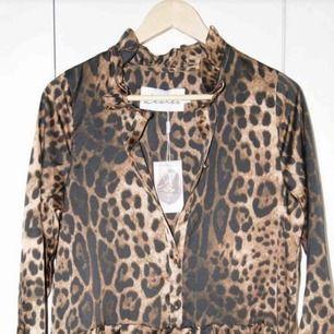 NY Leopardmönstrad klänning från LES LEVRES.   Knappar framtill. Volanger vid ärmslut ger en fin effekt.   Nypris 1.699kr. Storlek: 1 = 38. Material - Polyester