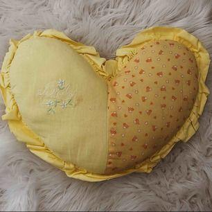 """Gul hjärtformad kudde med texten """"baby"""" på med massa små vita/orange hjärtan vid sidan, volang utanpå hjärtat"""