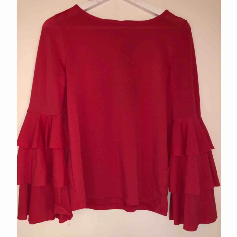 Otroligt fin tröja med volangärmar ifrån Gina Tricot. I nyskick. Hallonfärgad. Storlek S men skulle säga att den är mer som en M beroende på hur man vill att den ska sitta. . Blusar.