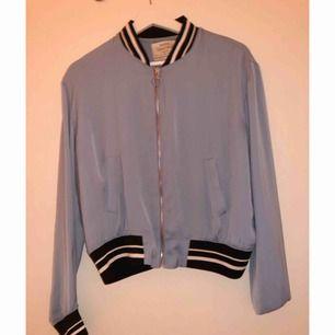 Babyblå superfin tunn bomberjacka/tröja ifrån Bershka. Vit och svartrandiga stripes. Använd 1 gång så i nyskick.