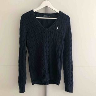 Mörkblå kabelstickad Ralph Lauren tröja. Använd men fortfarande fin.