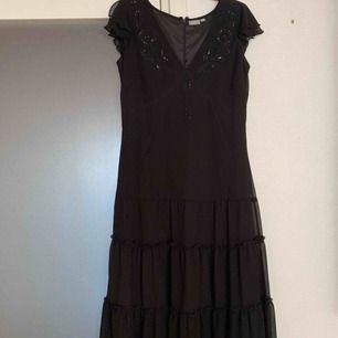 Snygg klänning med volang nertill och paljetter uppe fodrad  Storlek 42 Kan fraktas