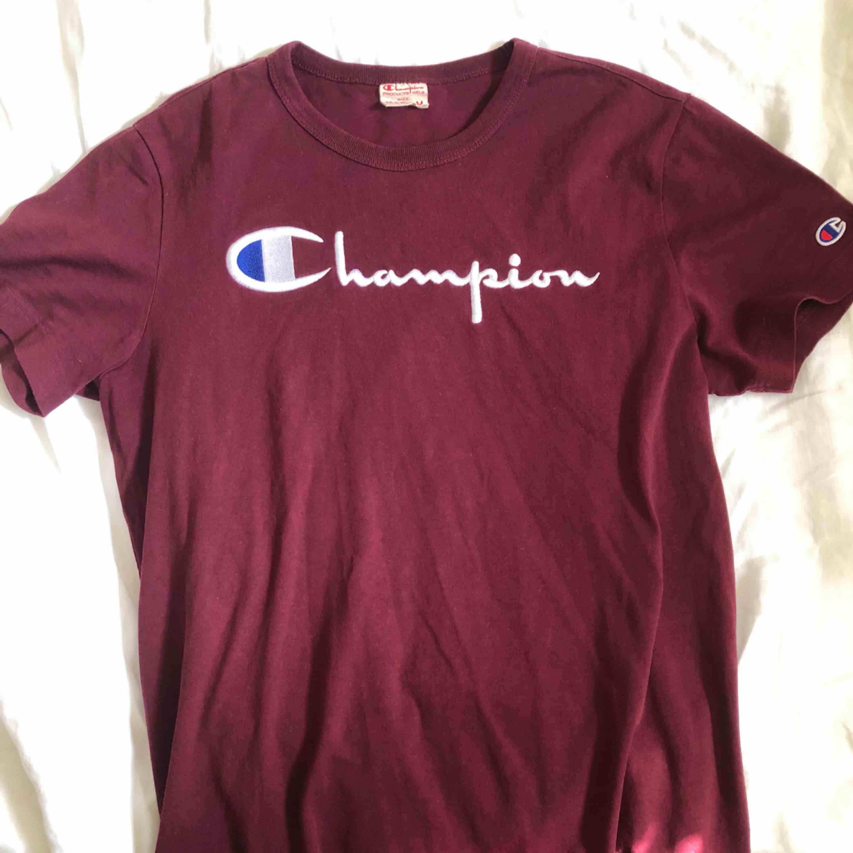 Skön vinröd Champion T-shirt med broderat märke över bröstet. Storlek M men passar även S! Mycket sparsamt använd . T-shirts.