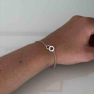 """Jättefint Evfa Attling armband, nästan aldrig använt. På en av ringarna står det """"Amor vincit omnia"""" vilket betyder """"kärlek övervinner allt"""". Äkta silver, ambandet kan bli 17cm eller 19cm. Orginalpris 900kr. Köpare står för frakt, betalning via swish."""
