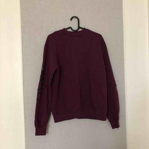 Fin vinröd sweatshirt med blomdetaljer på armarna (se bild 3) Knappt använt bara legat i garderoben! Priset kan diskuteras! Frakt tillkommer💕💕