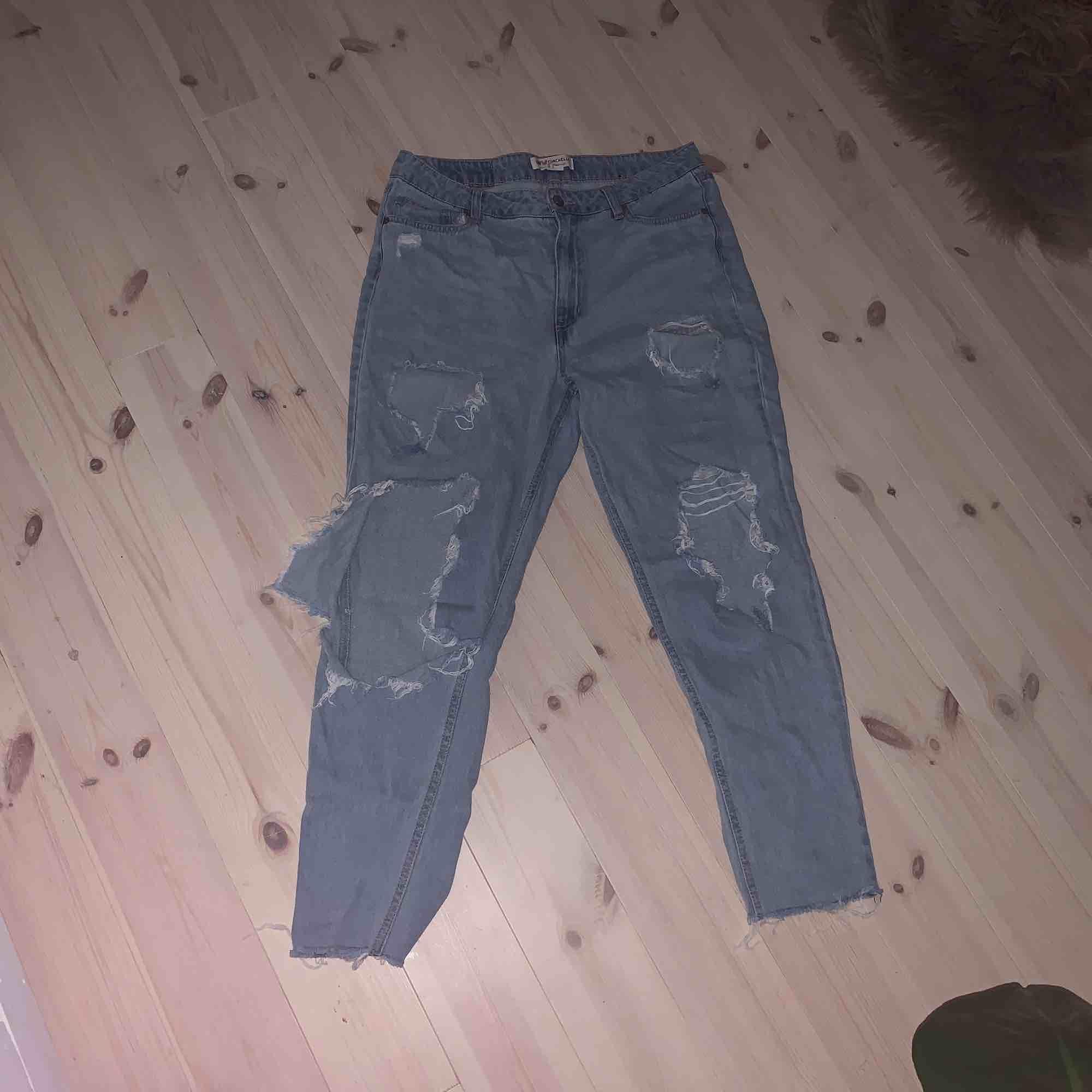 Suuupersnygga mom jeans med stora hål i! Står att det är storlek 42 men skulle säga att det är 38-40! Använda men i bra skick! Köparen står för frakt!. Jeans & Byxor.