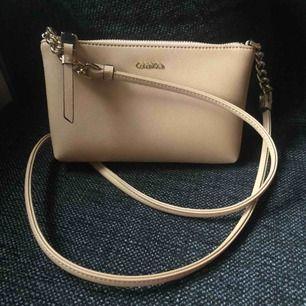 Beige väska från Calvin Klein. Äkta och köpt i USA. Som helt ny, endast använd en kväll.