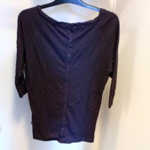 Mörklila tröja med knappar på baksidan och 3/4 ärm. Frakt tillkommer