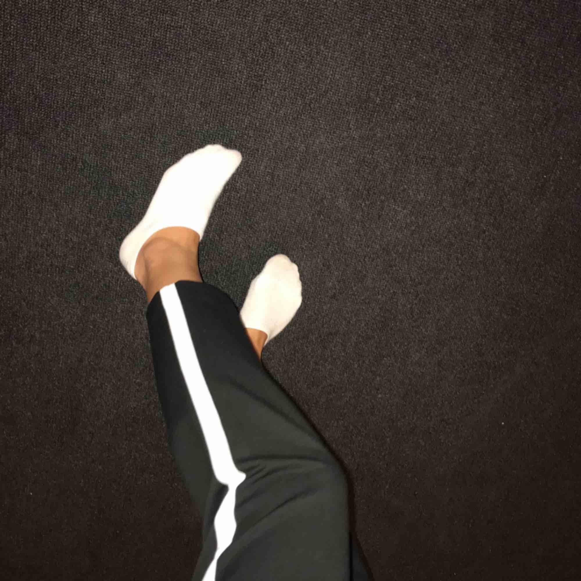 Svarta kostymbyxor med vit rand på benet från Zara. Kort i modellen. Använda typ 4 gånger, sälja pga används ej . Jeans & Byxor.