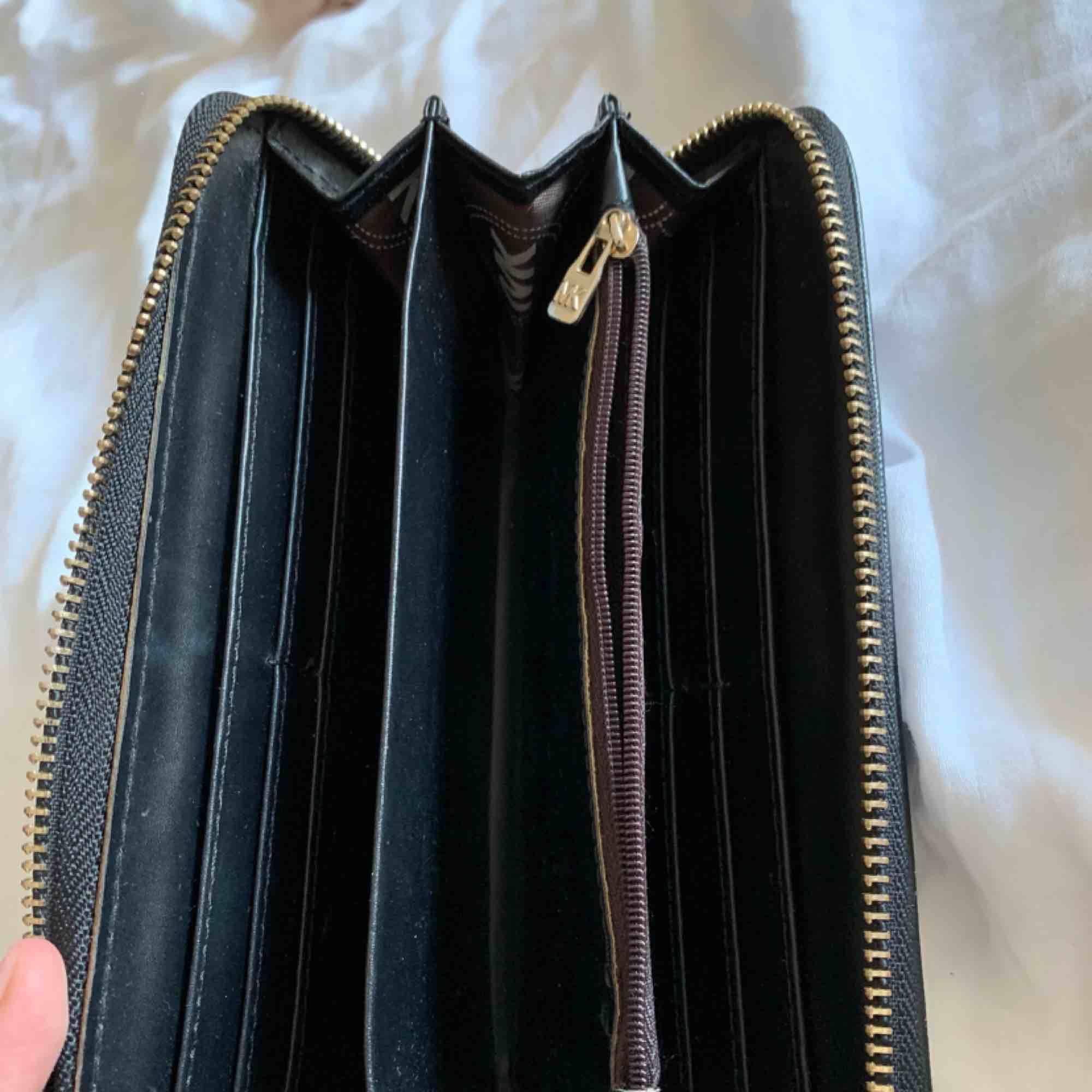 Falsk Michael Kors plånbok. Aldrig använd. Fint skick och snygg för att inte vara äkta. . Väskor.