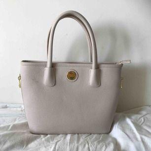 En beige/smutsrosa handväska från Don Donna. Väskan är inte i äkta läder och den är väldigt fint skick. Använd fåtal gånger. Axelband medföljer. Nypris:500kr  Kan frakta men då betalar du själv för frakten.