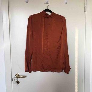 Skitsnygg roströd siden blus med högre krage och bell sleeved ärmar