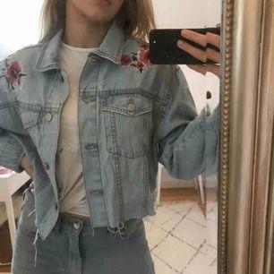 Croppad lite oversized jeansjacka med broderade detaljer ifrån Bershka i strl. M. Relativt välanvänd med fortfarande väldigt bra i kvalitén! Frakt tillkommer