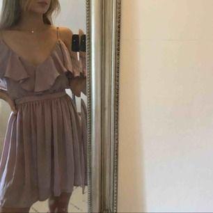 Rosa/lila klänning med volang detaljer från märket Oh My London, aldrig använd (prislapp kvar), säljes pga för stor i midjan för mig - annars hur fin som helst! Öppen i ryggen, frakt tillkommer!