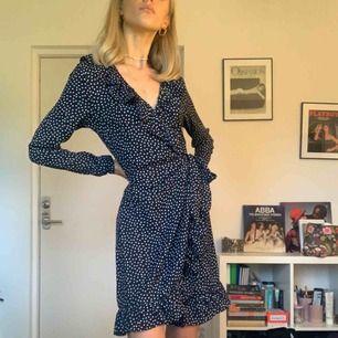 """Säljer en prickig söt Mörkblå klänning från NA-KD. Till ett par docs och en miniväska blir den super """"Devon Lee Carlson"""" -inspirerad! Jag är själv rätt liten , därför klänningen ser väldigt stor ut, men är i storlek 36."""