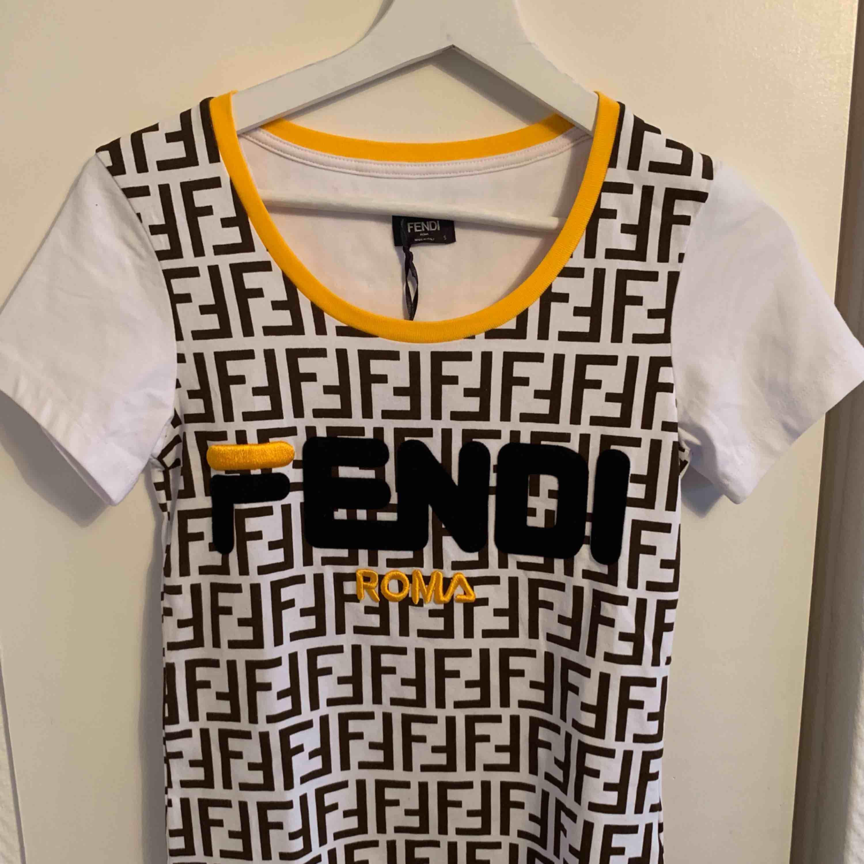 Oanvänd FENDI T-shirt för tjejer.  Storlek S  OBS: KÖPAREN STÅ FÖR FRAKTEN! . T-shirts.