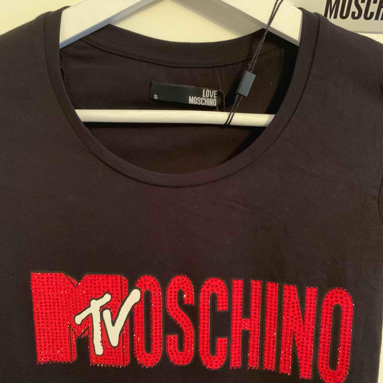 Oanvänd märkes t-shirt från MOSCHINO för tjejer Storlek: S  —— OBS: KÖPAREN STÅ FÖR FRAKTEN! . T-shirts.