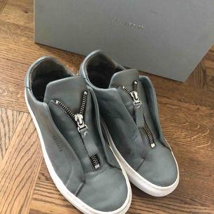 Ett par axel arigato skor i modell Clean 90 Zip sneaker. Använda en vår ungefär. Världens bekvämaste sko. Dragkedjan sitter fast och går inte att öppna men de sitter jättebra ändå och är super smidiga att sätta på.   Inköpspris: 1800kr