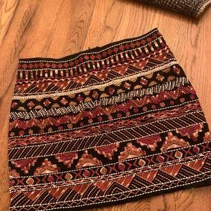 Snygg kjol från H&M med pärlor och broderier. Aldrig använd, prislapp kvar. Helsvart på baksidan.  Köparen betalar frakten.