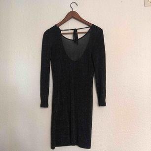 Transparent svart klänning med diskret glitter. Djupare rygg