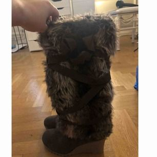 Fodrade vinterkängor med massa fuskpäls på. Dragkedja finns på insidan av skon. Använda en gång. Storlek 38. Skickas mot frakt.