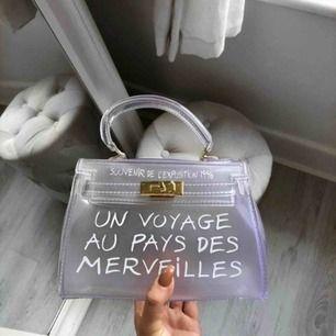En genomskinlig väska. Un Voyage Au Pays Des Merveilles står det på den. Stor storlek och får plats med en ipad. Aldrig använd!